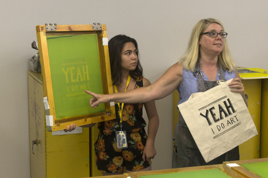 Student with a faculty member in screenprinting workshop at Pre-College Experience