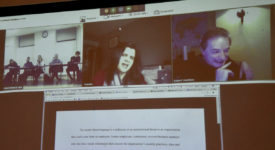 A screen shows business people video conferencing with Saint Rose students during a cybersecurity class.
