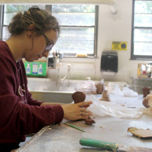 Female Saint Rose Pre-College Experience student sculpting in the studio.