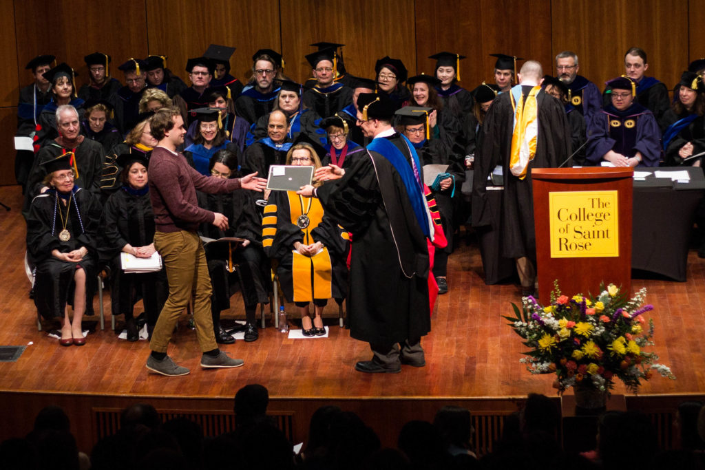 Student receiving award from Interim Dean Jeffrey Marlett at the Honors Convocation on March 24, 2018.