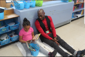 Tay Fisher reading with student in a classroom