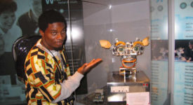 Ebah Patrick Ngole posing with a display case in an African-pattern shirt.